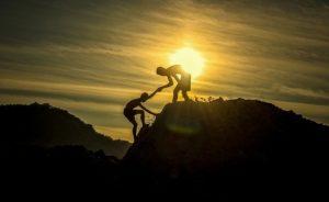 ひとりがもうひとりの手を引っ張って丘に登らせている写真。